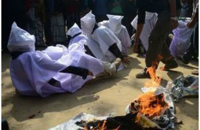 Parigi, sfilano abiti in fiamme contro le multinazionali del tessile